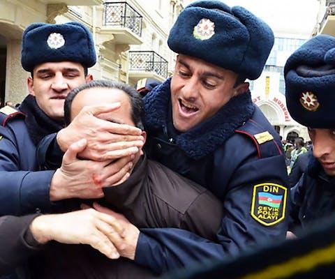 Politieagenten voeren in maart 2011 op ruwe wijze een politiek activist af bij een demonstratie in de Azerbeidzjaanse hoofdstad Baku
