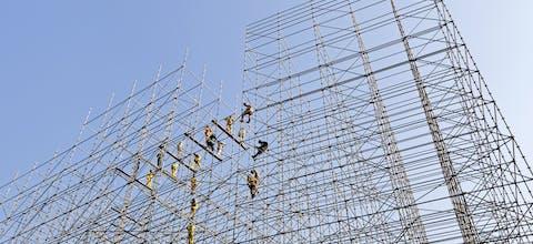 Bouwsteigers in de Qatarese hoofdstad Doha, waar vooral buitenlandse arbeiders de infrastructuur voor het WK voetbal van 2022 aanleggen, onder vaak mensonterende omstandigheden