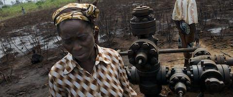 Een vrouw in de Nigerdelta in Nigeria staat bij een olieput die meermaals olie heeft gelekt