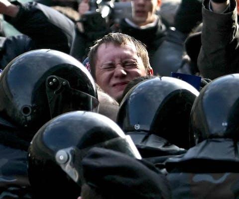 Een demonstrant raakt in de verdrukking bij een betoging in de Wit-Russische hoofdstad Minsk