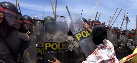Een student in Atjeh in Indonesië probeert een agent van de oproerpolitie weg te duwen