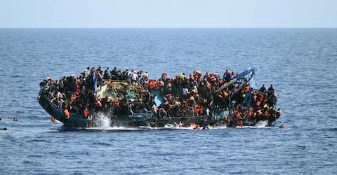 Migranten op een overvolle boot in de Middellandse Zee in mei 2016.