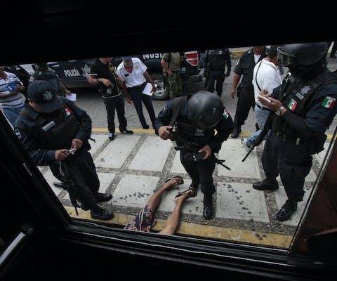 Politieagenten op de plek waar een jongen werd vermoord in Acapulco, Mexico. Het land wordt al geruime tijd geplaagd door drugsgerelateerd geweld.