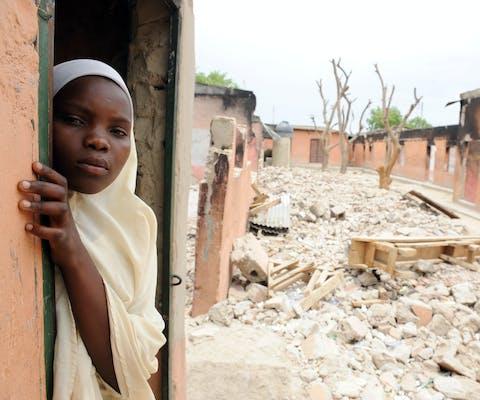Een scholiere bij een uitgebrand klaslokaal in noordoost Nigeria. De school is in brand gestoken door de gewapende groepering Boko Haram.