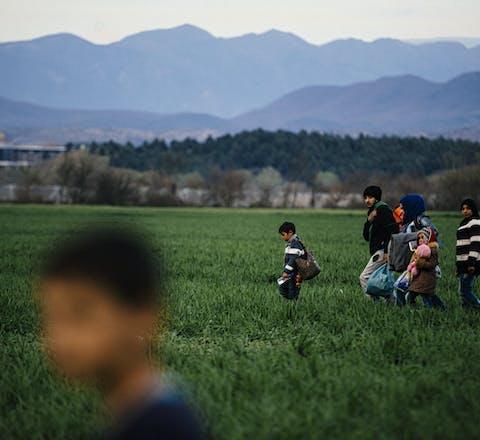 Vluchtelingen lopen door een veld in de buurt van een provisorisch vluchtelingenkamp nabij de Grieks-Macedonische grens