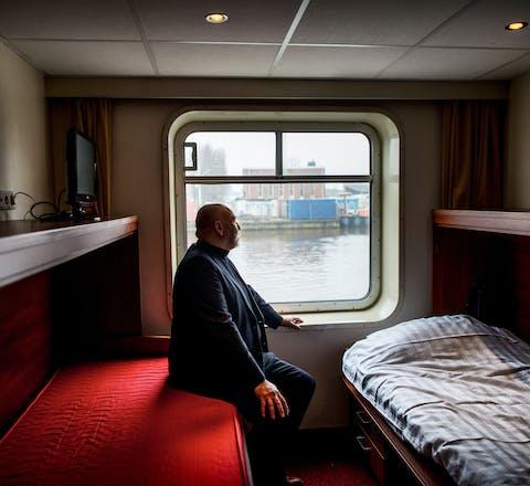 Groningen, 09-01-2017, Hotelschip Amanpuri voor uitgeprocedeerde asielzoekers legt aan bij Berlagebrug. Directeur John van Tilborg van bed-bad-broodopvang en als directeur van stichting Inlia , in 1 van de slaaphutten.