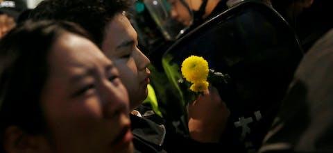 Een demonstrant met een bloem staat tegenover oproerpolitie in de Zuid-Koreaanse hoofdstad Seoul