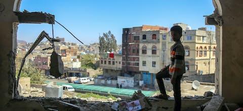 Een jongen uit de Jemenitische stad Taez staat in een gebouw dat gedeeltelijk verwoest is door een mortieraanval (3 februari 2016)