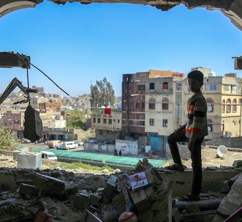 Een jongen uit de Jemenitische stad Taez staat in een gebouw dat gedeeltelijk verwoest is door een mortieraanval (3 februari 2016). Een coalitie onder aanvoering van Saudi-Arabië voert daar een oorlog tegen de Houthi's.