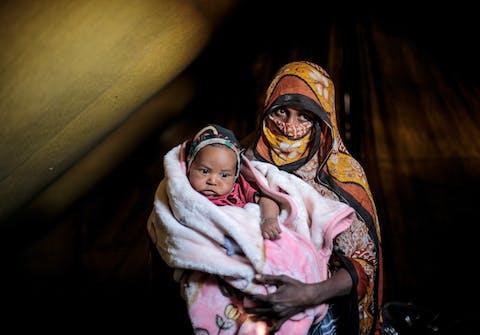 20 februari 2016: Um Abdulrahman draagt haar zoon van 10 maanden. Zij moesten vluchten toen hun huis geraakt werd door luchtaanvallen in de provincie Sada, grondgebied van de Huthi-milities. Ze leven nu in een vluchtelingenkamp in de nabijgelegen provincie Amran.