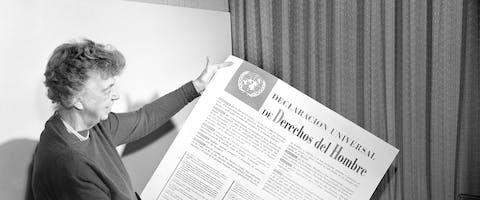 Eleanor Roosevelt bekijkt een poster met daarop de UVRM in het Spaans