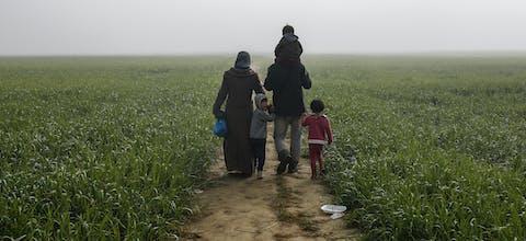 Een gezin loopt door de velden in de buurt van een provisorisch opvangkamp bij Idomeni, Griekenland.