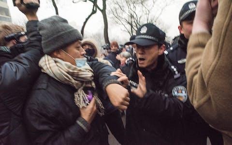 Chinese politieagenten duwen journalisten en aanhangers van mensenrechtenadvocaat Pu Zhiqiang opzij bij de rechtbank in Beijing. Hij stond terecht voor zijn kritiek op de Chinese communistische partij.
