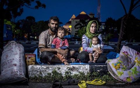 De Afghaanse asielzoeker Hasan Remezonei en zijn gezin op een parkeerplaats in de Indonesische stad Batam. Het aantal asielzoekers in Indonesië groeit; ze komen er vast te zitten, terwijl ze het liefst asiel zouden krijgen in landen als Nieuw-Zeeland en Australië.