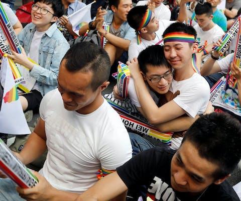 Demonstranten in Taiwan omhelzen elkaar nadat bekend werd gemaakt dat het constitutioneel hof besloot dat mensen van dezelfde sekse met elkaar mogen trouwen