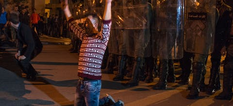 Demonstrators kneel before Moroccan police during a demonstration against corruption, repression and unemployment in the northern city of al-Hoceima on May 27, 2017. adel Senna/AFP/Getty Images