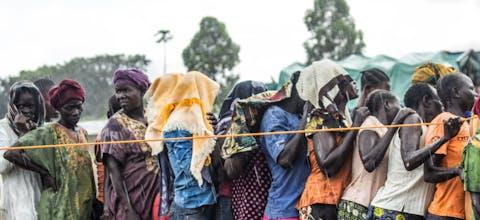Een groep vrouwen staan in de regen te wachten om zich te registreren bij een vluchtelingenkamp in Noord-Oeganda
