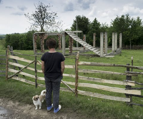 Een vrouw kijkt naar een vernietigd huis in Oost-Bosnië