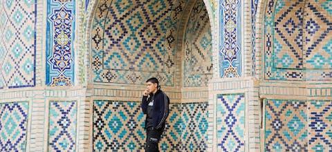 Telefonerende jongen bij een moskee in Oezbekistan.