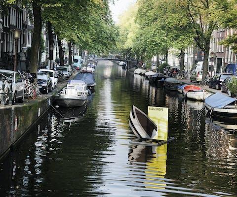 SOS Europe; zinkende bootjes in Amsterdamse grachten
