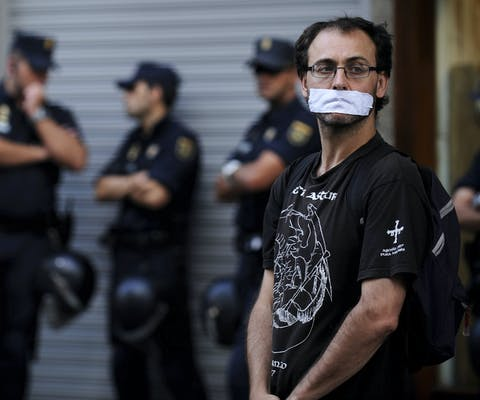 Een man protesteert met dichtgeplakte mond tegen de nieuwe, strengere Spaanse veiligheidswet (juni 2015). Tegenstanders van de wet vinden dat deze het recht op demonstreren schendt en de vrije meningsuiting aan banden legt.