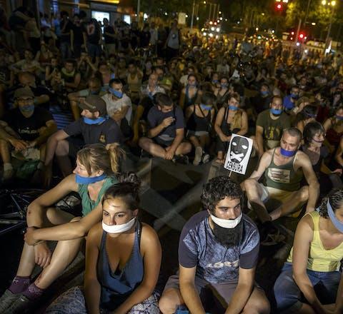 Demonstranten hebben hun mond afgeplakt tijdens een protestactie tegen een nieuwe veiligheidswet in Madrid in juli 2015.