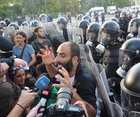 Vluchteling Ahmed H. praat met de media met achter hem de Hongaarse oproerpolitie. Plaats van handeling is een grensovergnag in 2015 waar de politie traangas en een waterkanon inzet om migranten te verhinderen het land binnen te komen.