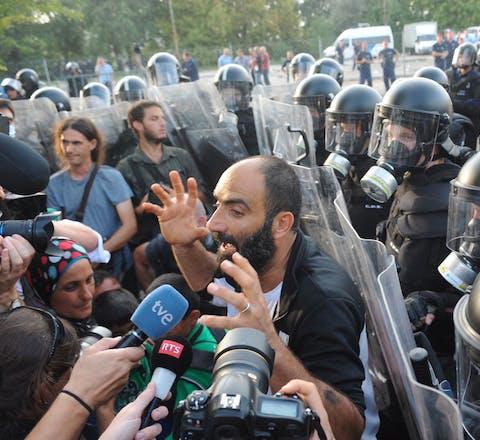 Ahmed H. praat in 2015 bij de grens tussen Servië en Hongarije met de media, met achter hem de Hongaarse oproerpolitie. De politie zette traangas en een waterkanon in om migranten te verhinderen het land binnen te komen.