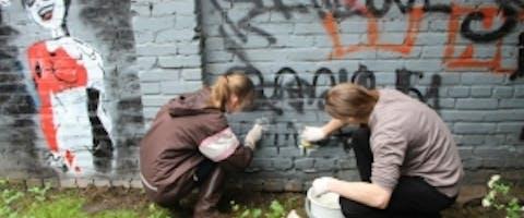 Studenten van Citizens Watch schilderen hatelijke symbolen op hun school weg