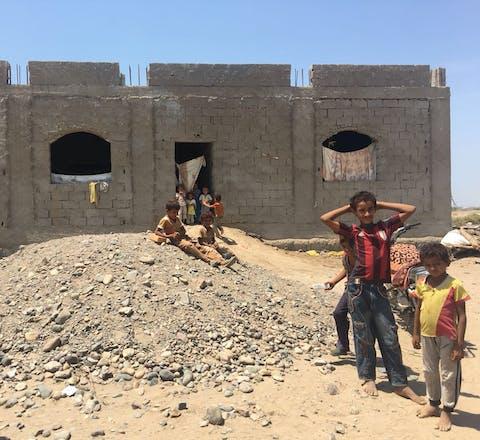 Spelende kinderen bij een half afgebouwd gebouw in Gawa'la, een woestijngebied buiten Aden. De kinderen zijn vluchtelingen uit de provincie Hodeidah.
