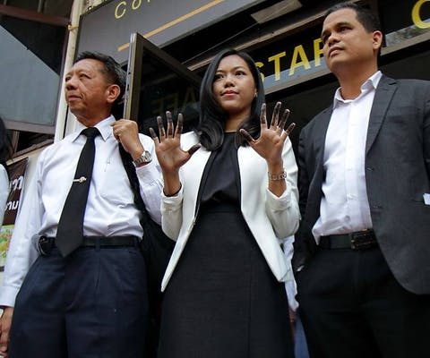 Thai lawyer Sirikan Charoensiri (also known as June) poses outside Chanasongkram Police Station in Bangkok, Thailand, to show press and activists her ink-stained fingers after hearing criminal charges being brought against her and submitting her fingerprints.