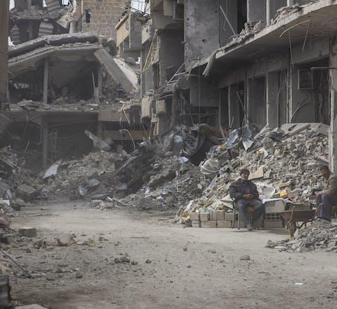 Twee inwoners van Raqqa te midden van de puinhopen.