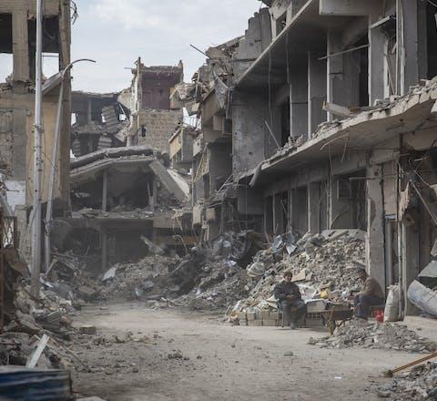 Twee inwoners van Raqqa tussen de puinhopen in hun verwoeste stad, februari 2018