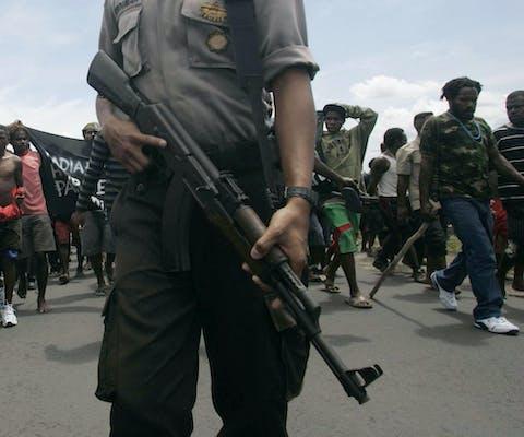 Een gewapende politieman houdt toezicht op een menigte demonstrerende Papoea's die de weg naar een vliegveld in de Indonesische provincie Papoea blokkeren. (2009).