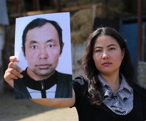 Bota Kussaiyn met een fot van haar vader die in een 'heropvoedingskamp'in China zit