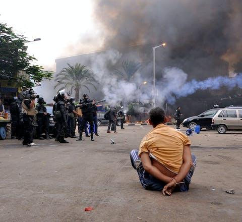 Een gehandboeide demonstrant op het Al-Nahdaplein in Caïro op 14 augustus 2013. Op de achtergrond gewapende veiligheidstroepen, die door Frankrijk geleverde wapens inzetten.