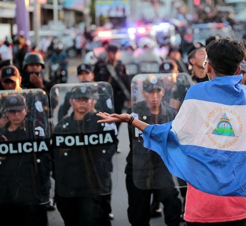 Een demonstrant tegen het bewind van president Daniel Ortega staat op 13 september 2018 tegenover de oproerpolitie in Managua, de hoofdstad van Nicaragua.