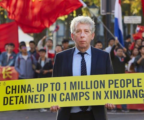 De voormalige directeur van Amnesty Nederland Eduard Nazarski demonstreert bij het Binnenhof voor mensenrechten en vrijheid in China.