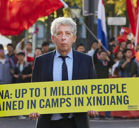 Amnesty Nederland directeur Eduard Nazarski demonstreert bij het Binnenhof voor mensenrechten en vrijheid in China.