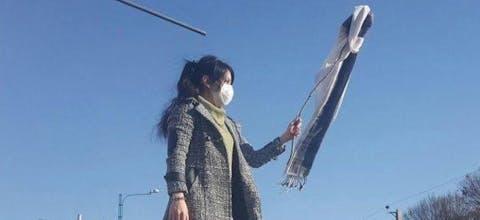 Een vrouw in de stad Karaj in Iran demonstreert tegen de hijab-wetten.