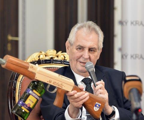 """De Tsjechische president Milos Zeman houdt een namaakgeweer omhoog met de tekst """"voor journalisten""""."""