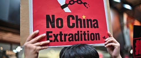 Een demonstrant houdt een bord omhoog uit protest tegen de plannen voor een nieuwe uitleveringswet in Hongkong