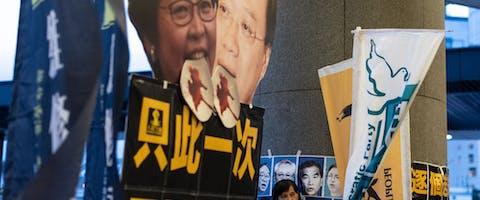 Een demonstrant staat voor een poster met een foto van de leider van Hongkong, Carrie Lam, tijdens een protest tegen de nieuwe uitleveringswet in Hongkong