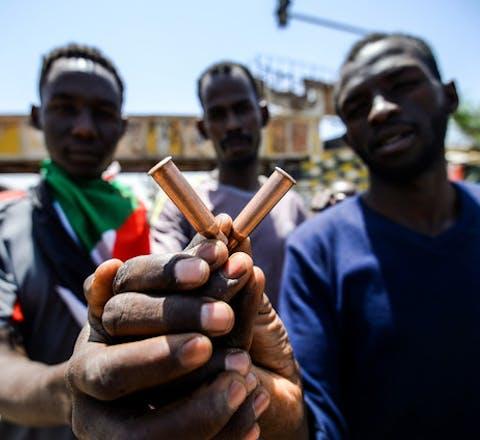 Een man toont de hulzen van kogels waarmee veiligheidstroepen in Sudan op vreedzame demonstranten schoten