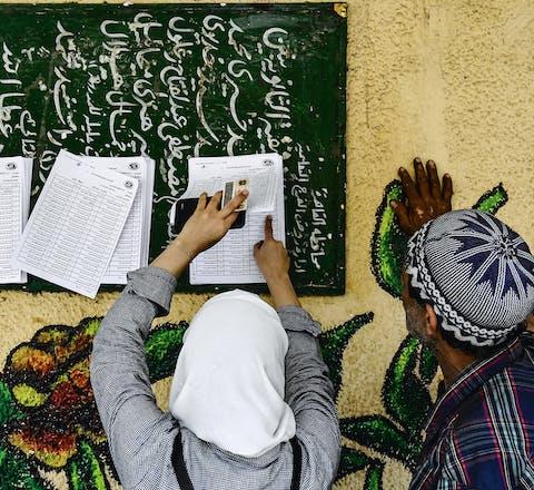 Egyptenaren zoeken hun naam op de lijst om te kunnen stemmen tijdens het referendum afgelopen april
