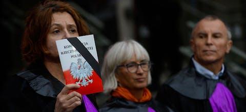 Een vrouw, gekleed als een rechter van het Hooggerechtshof hooud de Poolse grondwet omhoog om te protesteren tegen de hervoming van de rechtspraak die de onafhankelijkheid aantast