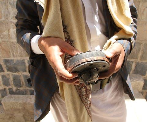Man laat een deel van een wapen zien dat werd gebruikt bij aanvallen op burgerdoelen in Sanaa, Jemen in 2015.