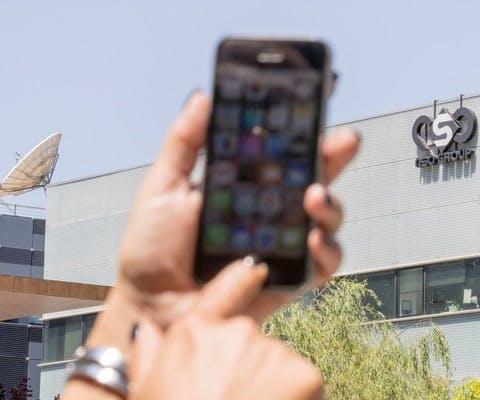 Een Israëlische vrouw met haar telefoon voor het kantoor van het beveilingingsbedrijf NSO Group dat spyware ontwkikkeld dat worden gebruikt om activisten aan te vallen