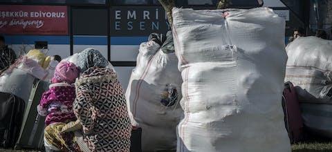 Een Syrische vrouw en kind wachten op de bus bij de Turks-Syrische grens