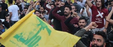 Supporters van de sjiitische Hezbollah-beweging steunen hun leider Hassan Nasrallah. In een televisietoespraak zei hij dat het terugtreden van de regering zal leiden tot 'chaos en het instorten' van de economie, 25 oktober 2019. © Ibrahim Amro/AFP via Getty Images
